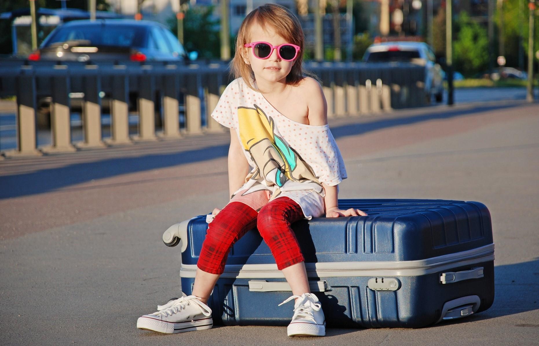 Niña sentada sobre una maleta