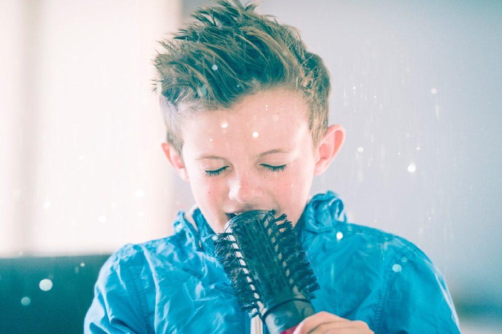 Niño rubio canta, utilizando un cepillo de pelo como micrófono